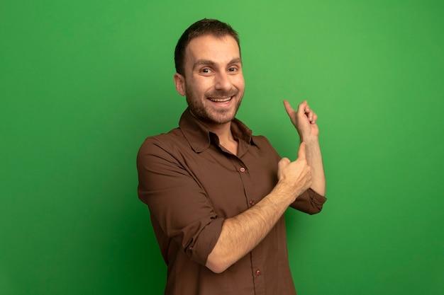 コピースペースで緑の背景に分離された後ろを指しているカメラを見てうれしそうな若い白人男性