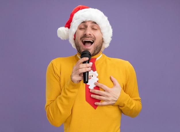 Радостный молодой кавказский мужчина в рождественской шляпе и галстуке держит микрофон и поет с закрытыми глазами, держа руку на груди, изолированной на фиолетовом фоне