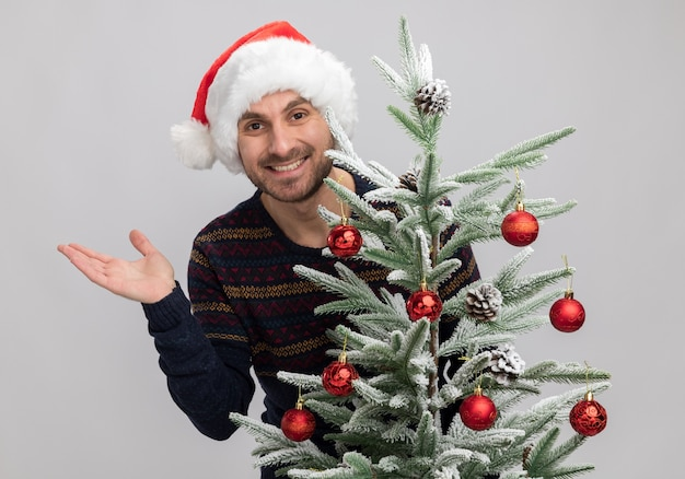 Joyful young caucasian man wearing christmas hat standing behind christmas tree looking at camera showing empty hand isolated on white background