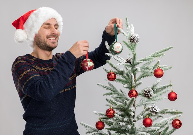 Joyful young caucasian man wearing christmas hat standing near christmas tree decorating it with christmas ornament balls laughing with closed eyes isolated on white background