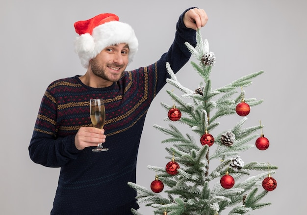 Joyful young caucasian man wearing christmas hat standing near christmas tree holding glass of champagne looking at camera grabbing branch of tree isolated on white background