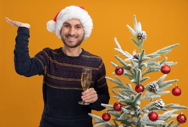 Gioioso giovane uomo caucasico che indossa il cappello di natale in piedi vicino all'albero di natale decorato tenendo il bicchiere di champagne guardando la telecamera che mostra la mano vuota isolata su sfondo arancione