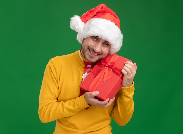 Gioioso giovane uomo caucasico indossando cravatta natalizia e cappello tenendo il pacchetto regalo guardando la telecamera isolata su sfondo verde