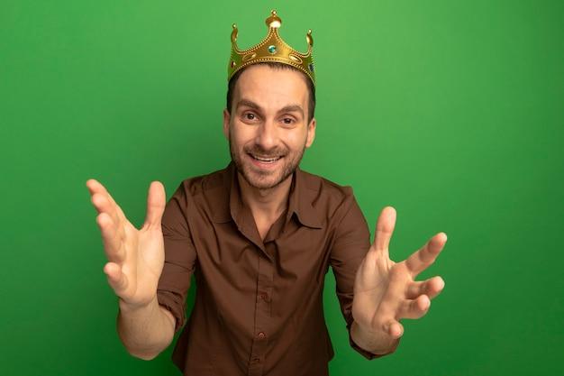 緑の背景に分離されたカメラに向かって手を伸ばしてカメラを見て王冠を身に着けているうれしそうな若い白人男性
