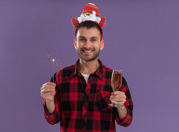 Радостный молодой кавказский человек в головной повязке санта-клауса держит праздничный бенгальский огонь и бокал шампанского, глядя в камеру, изолированную на фиолетовом фоне