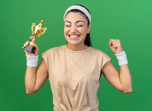 머리띠를 하고 우승자 컵을 들고 있는 즐거운 백인 스포티 소녀는 녹색 벽에 격리된 닫힌 눈으로 예 제스처를 취합니다.