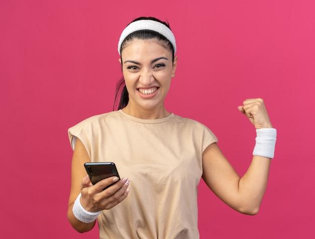 Радостная молодая кавказская спортивная девушка с повязкой на голову и браслетами, смотрящая вперед, держит мобильный телефон и делает жест да, изолированный на розовой стене