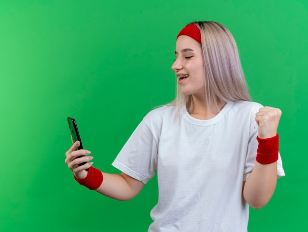 Радостная молодая кавказская спортивная девушка с подтяжками, носящая повязку на голову и браслеты держит кулак и смотрит на телефон