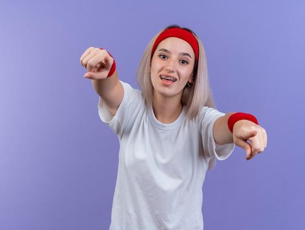 Радостная молодая кавказская спортивная девушка с подтяжками, носящая повязку на голову и браслеты, смотрит и указывает на камеру двумя руками на фиолетовом