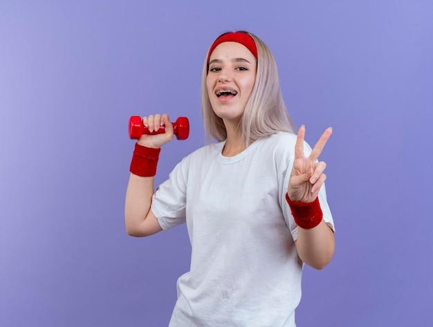 머리띠를 착용 중괄호와 즐거운 젊은 백인 스포티 한 소녀