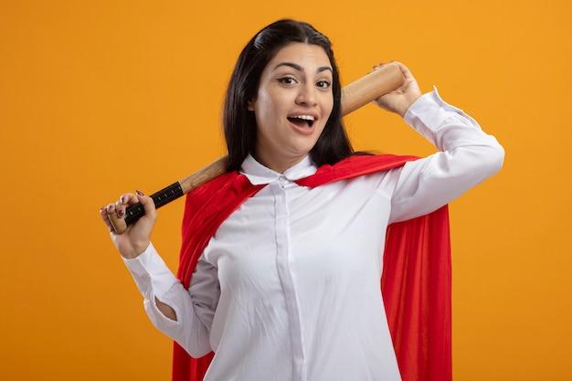 Радостная молодая кавказская девушка супергероя держит бейсбольную биту за шею, глядя в камеру, изолированную на оранжевом фоне