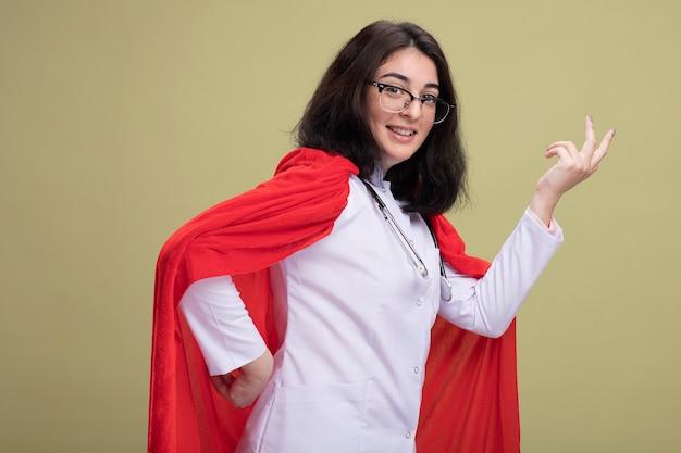 医者の制服と聴診器を身に着けている赤いマントのうれしそうな若い白人のスーパーヒーローの女の子は、オリーブグリーンの壁に隔離された空気中に手を保ちながら縦断ビューで立っています