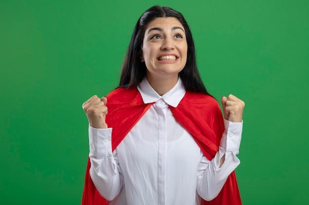 Радостная молодая кавказская девушка супергероя, глядя вверх, делает жест да, изолированные на зеленом фоне с копией пространства