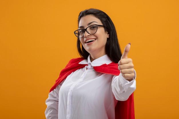 Gioiosa giovane ragazza caucasica del supereroe con gli occhiali in piedi nella vista di profilo che guarda l'obbiettivo che mostra pollice in su isolato su priorità bassa arancione con lo spazio della copia