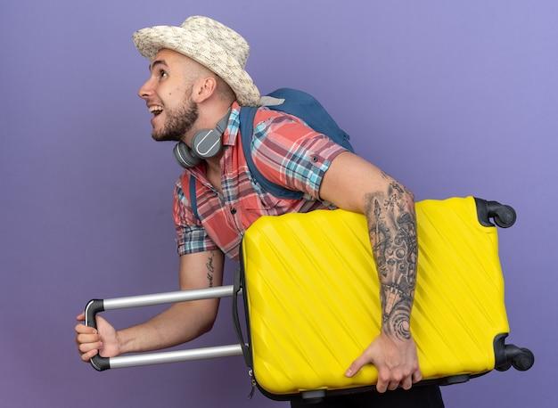 Gioioso giovane viaggiatore caucasico con cappello da spiaggia di paglia e con zaino in piedi di lato tenendo la valigia isolata su sfondo viola con spazio di copia