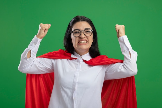 Gioiosa giovane indoeuropea vincitore supereroe ragazza con gli occhiali stringendo i suoi pugni alzati sorridente isolato sulla parete verde