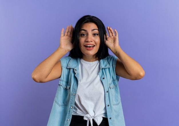Gioiosa giovane donna caucasica tiene le mani vicino alla testa isolata su sfondo viola con copia spazio