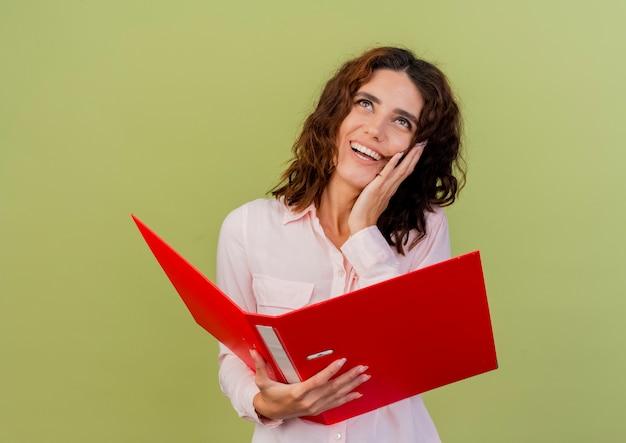 Радостная молодая кавказская женщина кладет руку на лицо, глядя вверх и держа папку с файлами, изолированную на зеленом фоне с копией пространства