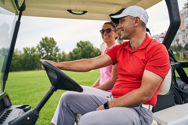 Joyful young caucasian woman riding in a golf car with a smiling middle-aged male instructor