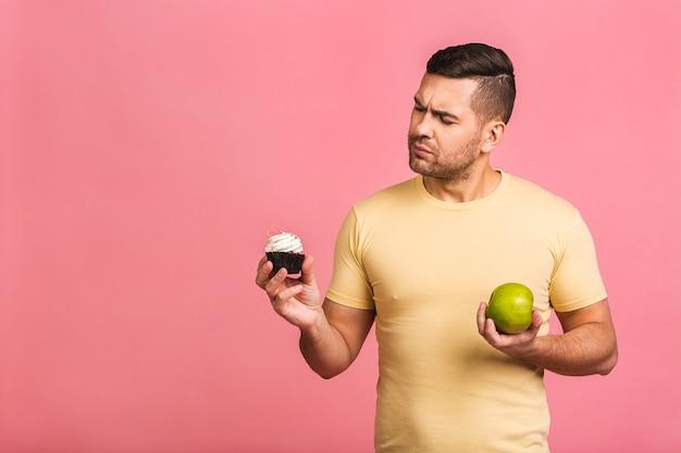 Радостный молодой кавказец в повседневной одежде ошибся, сделав выбор между тортом и свежим зеленым яблоком