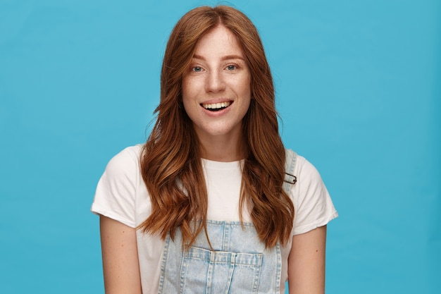 Joyful young charming redhead woman with natural makeup looking gladly at camera with broad sincere smile, being in nice mood while posing over blue background