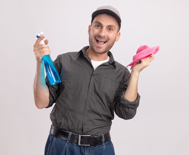 Gioioso giovane uomo delle pulizie che indossa abiti casual e berretto in possesso di spray per la pulizia e straccio in piedi felice ed eccitato sopra il muro bianco