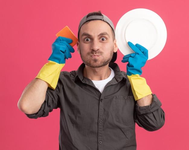 Gioioso giovane uomo delle pulizie che indossa abiti casual e berretto in guanti di gomma che tengono piatto e spugna che soffia guance in piedi sopra la parete rosa