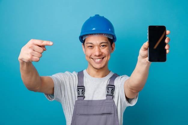 安全ヘルメットとそれを指しているカメラに向かって携帯電話を伸ばしている制服を着てうれしそうな若い建設労働者