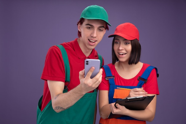 Joyful young couple in construction worker uniform and cap guy holding mobile phone girl holding pencil and clipboard both looking at mobile phone isolated on purple wall