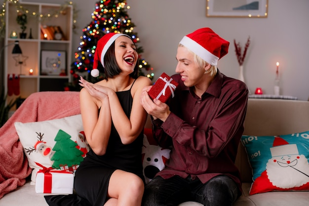 Gioiosa giovane coppia a casa nel periodo natalizio indossando il cappello della santa seduto sul divano in soggiorno che riceve i regali