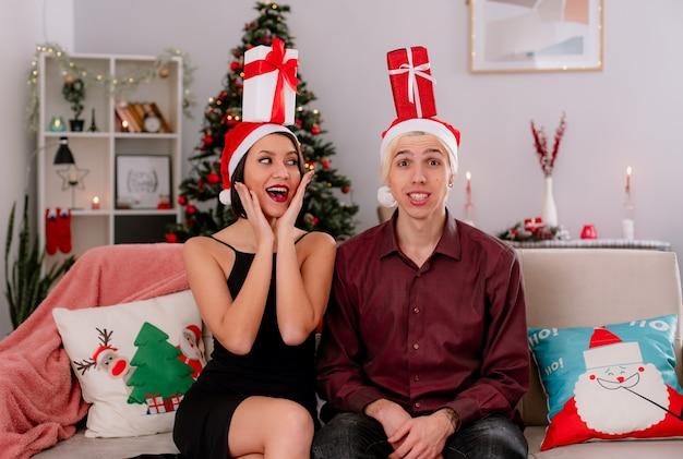 Gioiosa giovane coppia a casa nel periodo natalizio indossando il cappello della santa seduto sul divano con pacchetti regalo sulla loro testa in soggiorno ragazza mantenendo le mani sul viso guardando ragazzo