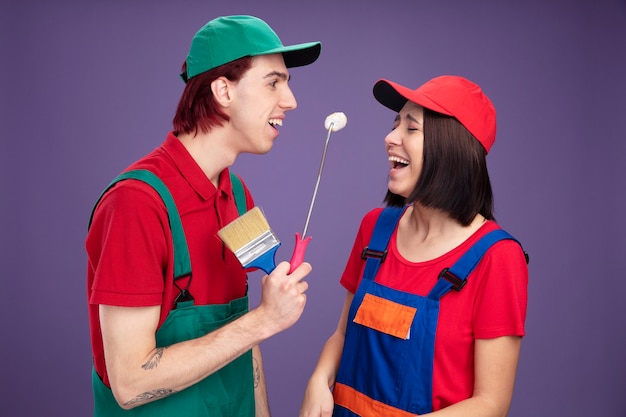 건설 노동자 유니폼을 입은 즐거운 젊은 부부와 페인트 롤러와 페인트 브러시를 들고 있는 모자 남자와 닫힌 눈으로 웃는 소녀와 소녀를 바라보는 남자