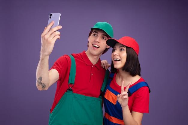 건설 노동자 유니폼을 입은 즐거운 젊은 부부와 셀카를 찍는 모자를 쓴 소녀가 평화 사인을 하는 남자의 어깨에 손을 얹고 있다