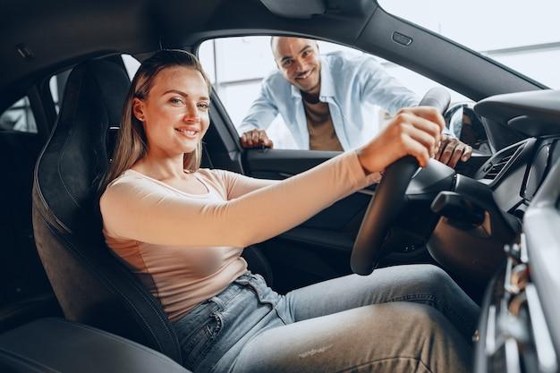 新しい車の中を見回すうれしそうな若いカップル