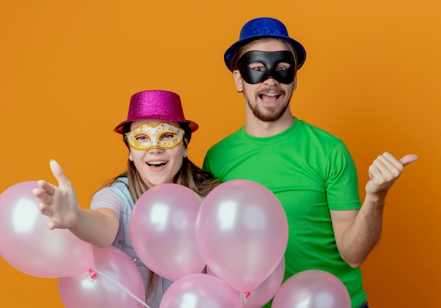 Joyful young couple stands with helium balloons girl in pink hat wearing masquerade eye mask points forward with hand handsome man in blue hat wearing masquerade eye mask points at side