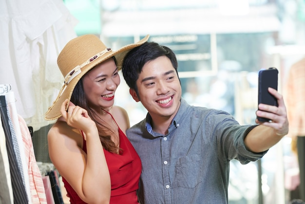 一緒に買い物をするときにデパートで自分撮りをしているうれしそうな若いカップル