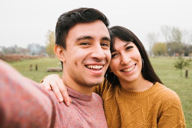 Joyful young couple taking selfie