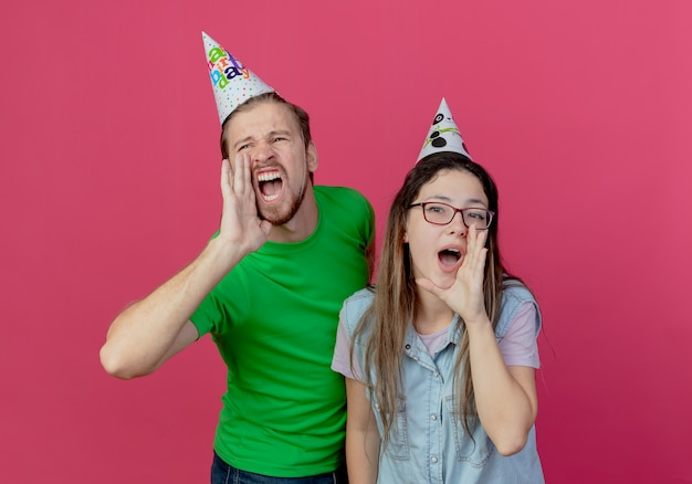 Joyful young couple wearing party hat holds hand close to mouth pretending to call someone isolated on pink wall
