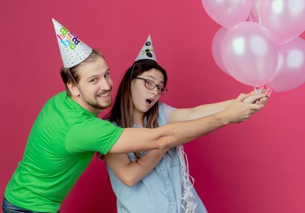 パーティーハットをかぶってうれしそうな若いカップルはピンクの壁に孤立して見えるヘリウム気球を保持します