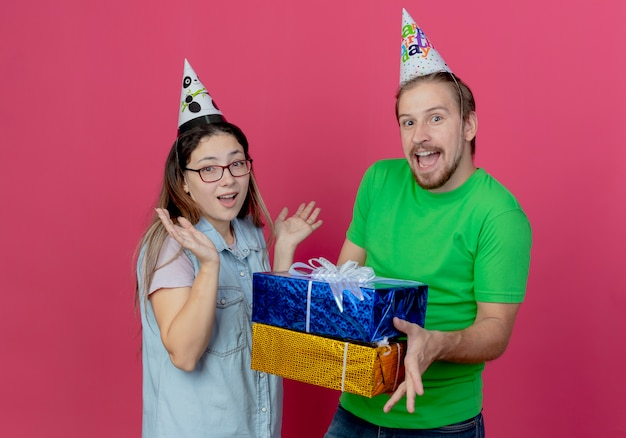Joyful young couple wearing party hat looks man holds gift boxes and girl raises hands isolated on pink wall