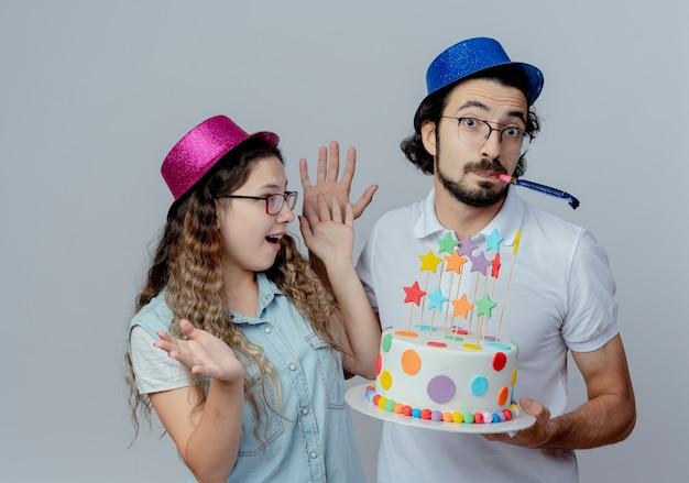 ピンクと青の帽子の男を身に着けているうれしそうな若いカップルは女の子に誕生日ケーキを与え、白い背景で隔離の笛を吹く