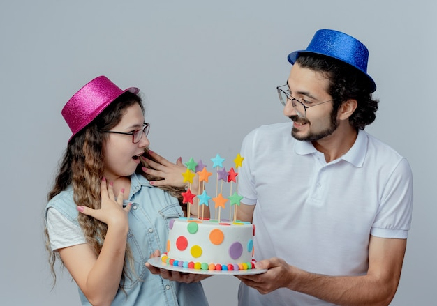 Joyful young couple wearing pink and blue hats guy gives birthday cake to girl