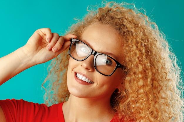 Радостная молодая кудрявая женщина в очках улыбается крупным планом
