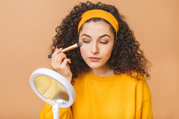 Joyful young curly woman is sapplying foundation cream on her skin. she is looking at mirror in her hand. isolated on beige background