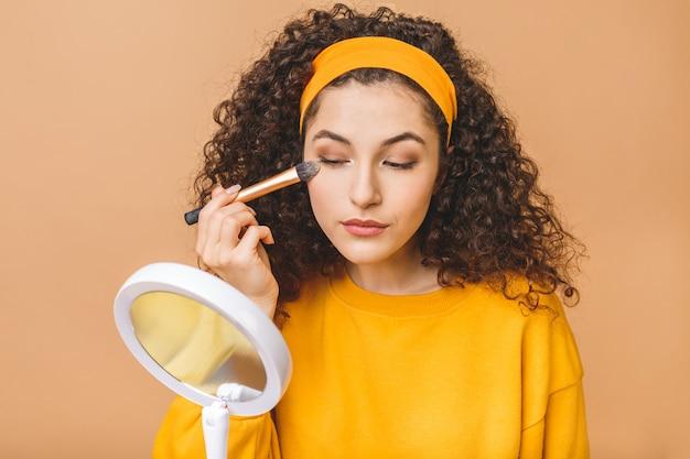 Радостная молодая кудрявая женщина наносит тональный крем на кожу. она смотрит на зеркало в руке. изолированные на бежевом фоне