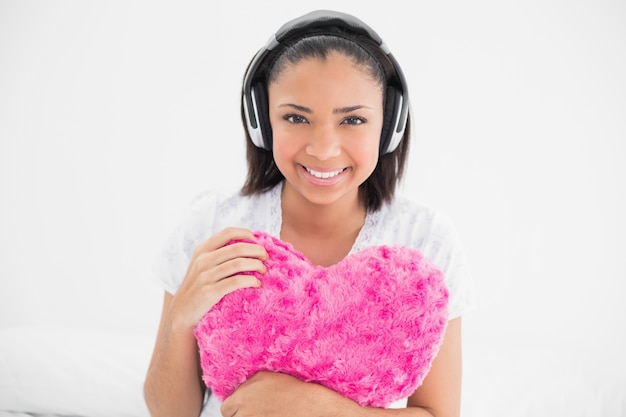 Joyful young dark haired model cuddling a pillow and listening to music