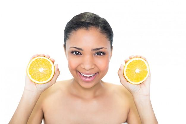 Joyful young dark haired model holding orange halves