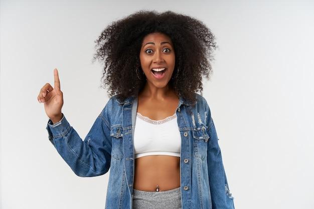巻き毛のうれしそうな若い暗い肌の女性は、幸せにそして広く笑って、元気で、人差し指を上げたカジュアルな服を着て白い壁の上に立っています