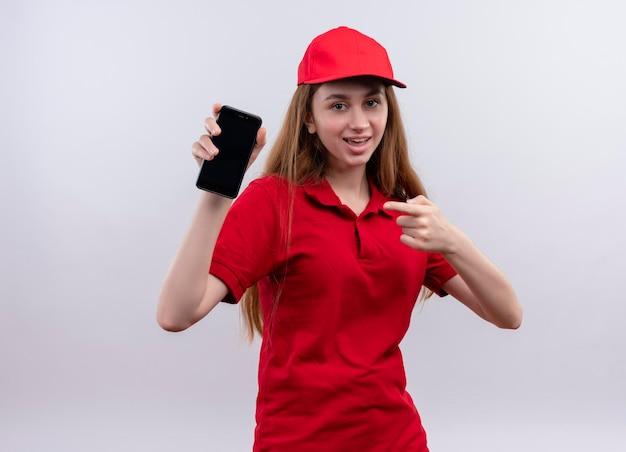 Радостная молодая доставщица в красной форме держит и указывая на мобильный телефон на изолированном белом пространстве