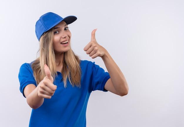 파란색 유니폼을 입고 즐거운 젊은 배달 소녀 복사 공간이 흰 벽에 고립 된 그녀의 엄지 손가락을 모자